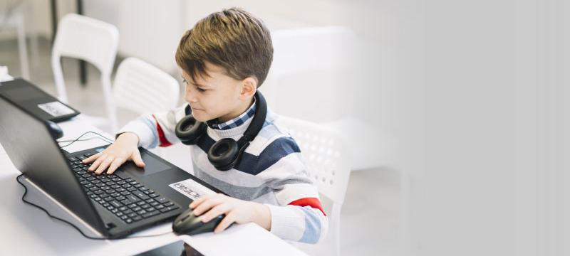 Image contains photograph of a small boy interacting with a laptop