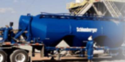 Image contains a partially blurred photograph of a Schlumberger's wheeled oil transportation container and a company's field worker standing aside of it.