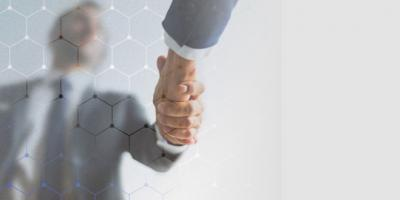 Banner about 'Interamerican Alliance for Competition Protection' article. Image contains photograph of two men shaking hands seen from below.